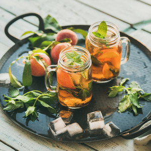 Summer refreshing cold peach ice tea on tray  square crop