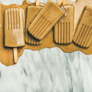Flatlay of melting coffee latte popsicles  square crop