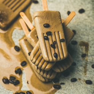 Melting coffee latte popsicles with roasted coffee beans