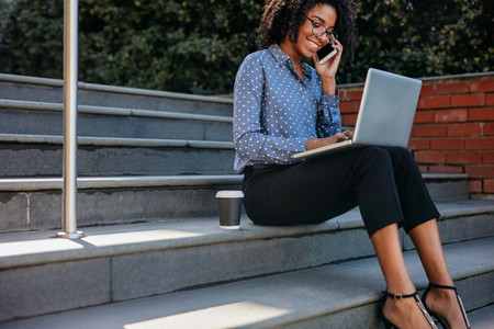 Businesswoman on steps with phone and laptop