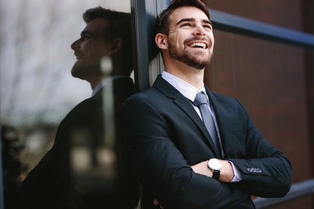 Cheerful businessman standing outside office building