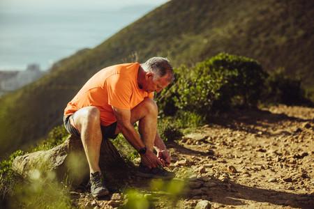 Trail runner taking a break tying shoe lace