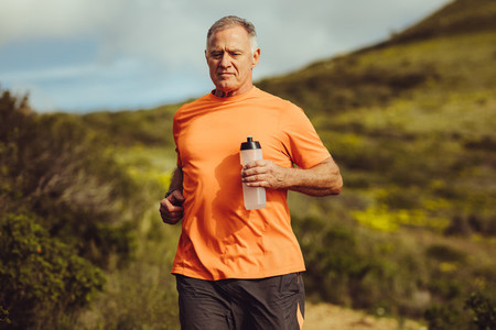 Senior man in fitness clothes running outdoors