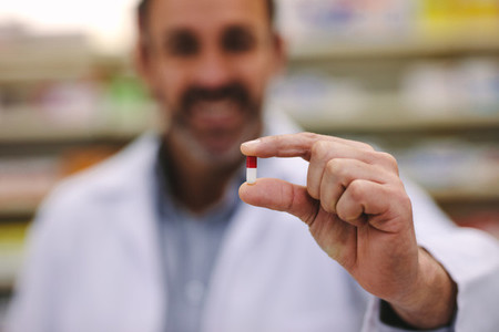 Male pharmacist holding a pill