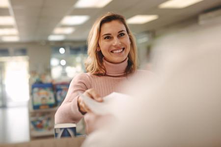 Customer giving prescription to chemist in pharmacy