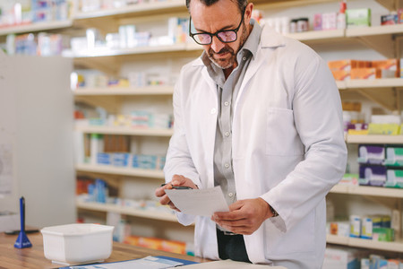 Mature male chemist working in drug store