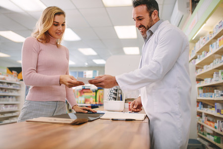 Chemist taking prescription from customer at pharmacy