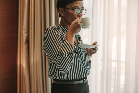 Businesswoman on business trip drinking coffee in hotel room