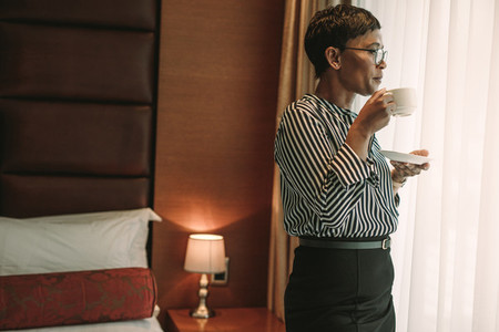 Businesswoman standing in hotel room drinking coffee