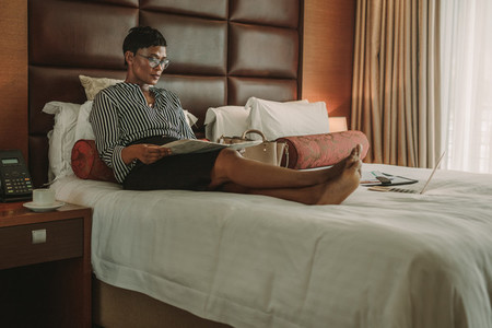 Businesswoman reading a newspaper in modern hotel room