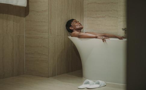 Mature african woman lying in bathtub