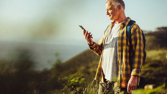 Man looking at mobile phone standing on a hill