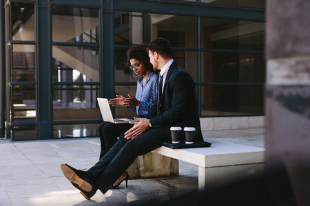 Two business people discussing work with laptop