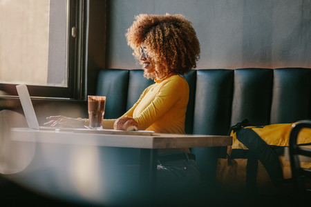Freelancer woman working on laptop sitting at a restaurant