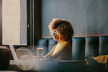 Smiling afro american woman sitting at a cafe working on laptop