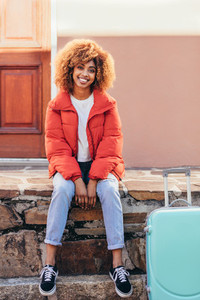 Smiling female traveller sitting outdoors with her luggage