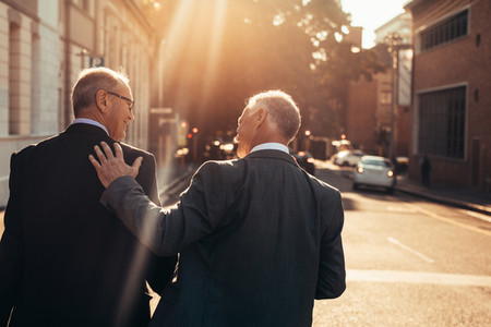 Two senior business people walking outdoors