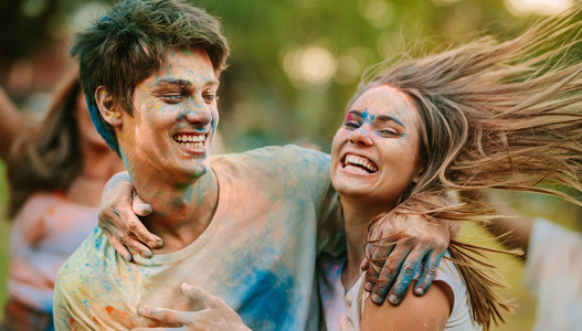 Happy couple playing holi together and having fun