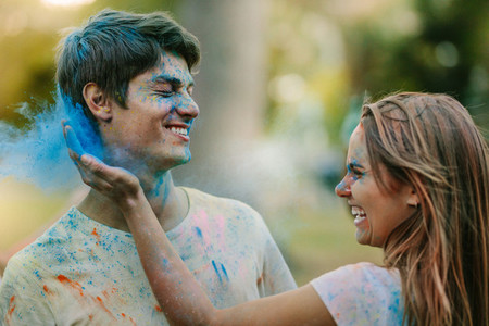 Couple playing holi in a park