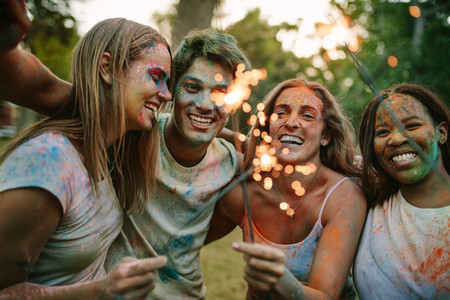 Group of friends burning fire sparkles while playing holi