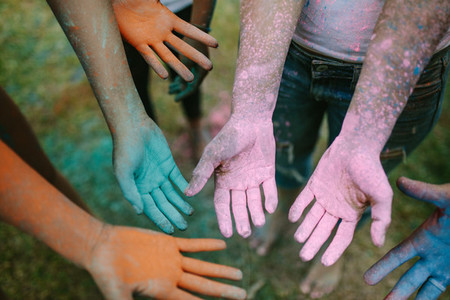 Top view of hands of people smeared with holi colours