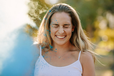 Portrait of a smiling woman playing holi