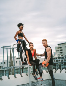 Fitness people relaxing after workout on rooftop
