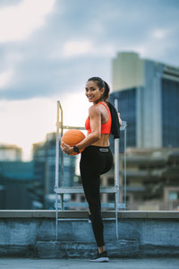 Fitness woman standing on rooftop holding a basketball