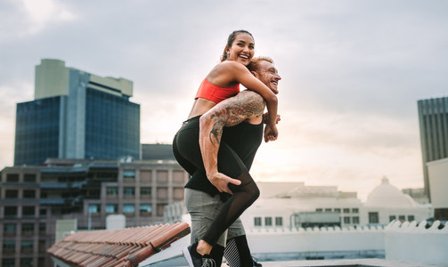 Female athlete piggy riding on a man while training on rooftop