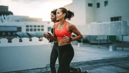 Fitness women running together on rooftop