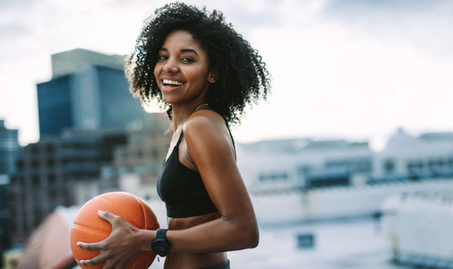 Portrait of a fitness woman holding a basketball