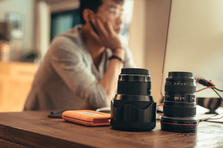 Photographer editing photos with lenses on table