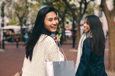 Smiling women walking around the city shopping