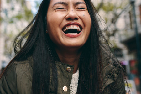 Close up of an asian woman laughing