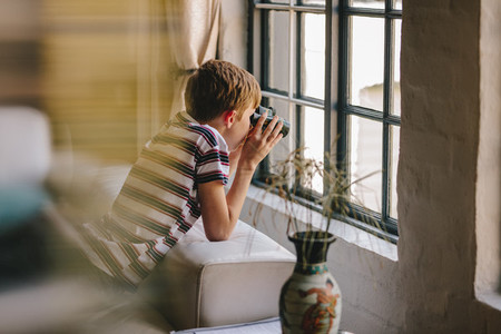 Curious boy looking out the window with binocular