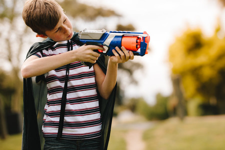 Boy playing super hero boy with gun