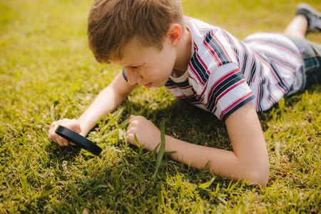 Boy exploring garden grass with his magnifier
