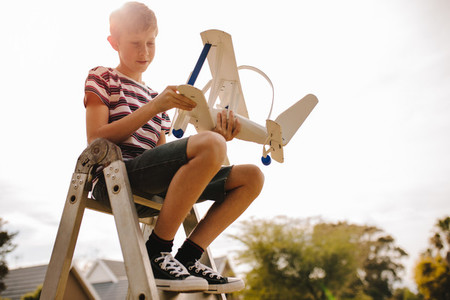 Boy siting on ladder with toy airplane