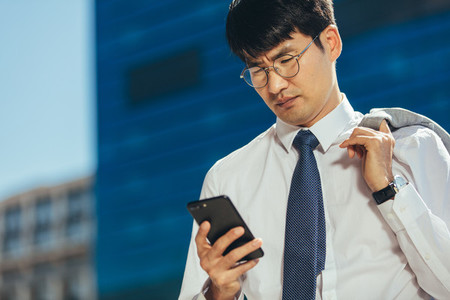 Businessman reading text message on his mobile phone outdoors