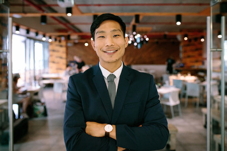 Confident young businessman standing at coffee shop