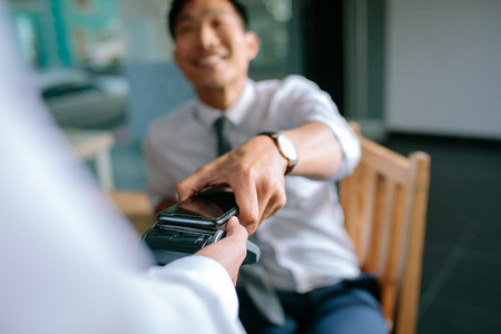 Businessman paying bill through smartphone using NFC technology