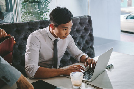 Businessman busy working on laptop at cafe