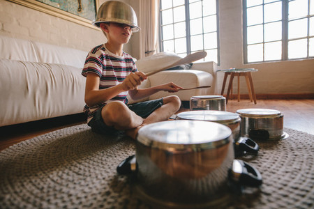 Boy playing drums on kitchenware at home