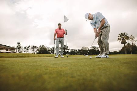 Senior men playing golf on the green