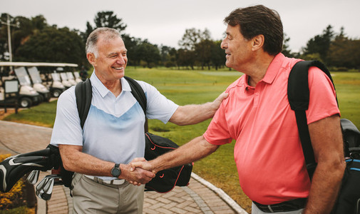 Mature golfers meeting at the golf course and shaking hands