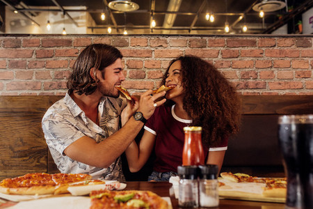 Loving couple feeding each other pizza