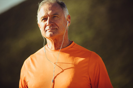 Close up of a senior man standing outdoors listening to music