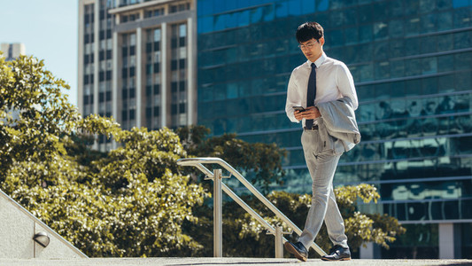 Businessman walking and using a smart phone outdoor