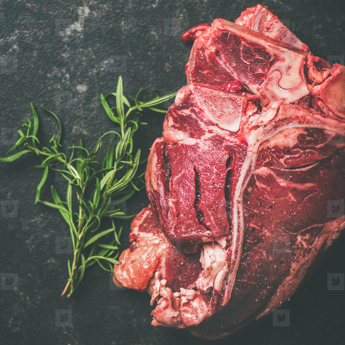 Fresh raw beef meat t bone steaks with rosemary  square crop