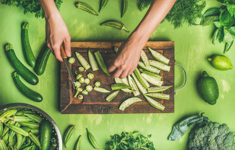 Flat lay of healthy green vegan cooking ingredients on board